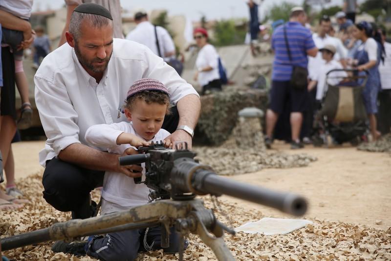 israeli man and son with machine gun